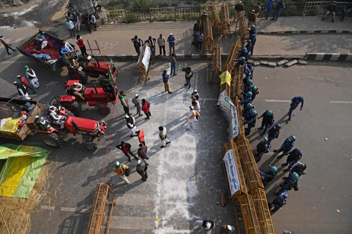 """Farmers gather next to their tractors as police stand guard at a roadblock, to stop them from marching to New Delhi to protest against the central government's agricultural reforms, in Ghazipur, India, on Dec. 1, 2020.span class=""""copyright""""Sajjad Hussain— AFP/Getty Images/span"""