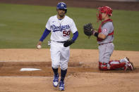 Los Angeles Dodgers' Mookie Betts, left, scores as Cody Bellinger was walked by Los Angeles Angels starting pitcher Julio Teheran during the first inning of a baseball game Saturday, Sept. 26, 2020, in Los Angeles. (AP Photo/Ashley Landis)