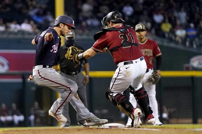 Arizona Diamondbacks catcher Stephen Vogt, right, attempts to tag Washington Nationals' Trea Turner, left, in a rundown between third base and home plate during the eighth inning of a baseball game Sunday, May 16, 2021, in Phoenix. Diamondbacks' Vogt missed the tag but Nationals' Turner was ruled out of the baseline for an out. (AP Photo/Ross D. Franklin)