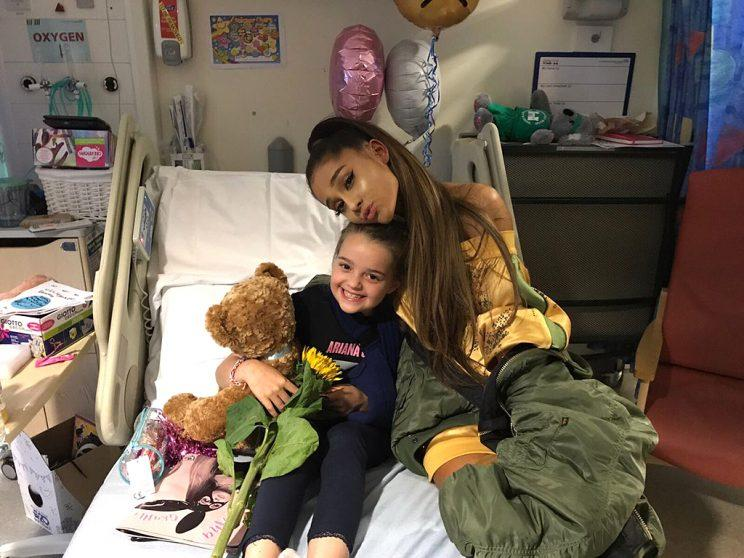 Ariana Grande cuddled with 8-year-old Lily Harrison. (Photo: Adam Harrison via Twitter)