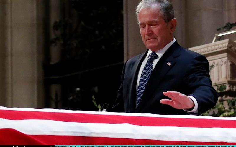 George W Bush touches the casket of his father George H W Bush during a funeral ceremony - Getty Images North America