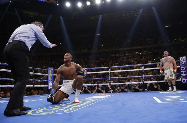 Andy Ruiz, right, watches as the referee counts to British boxer Anthony Joshu, center, during the third round of a heavyweight championship boxing match Saturday, June 1, 2019, in New York. Ruiz won in the seventh round. (AP Photo/Frank Franklin II)