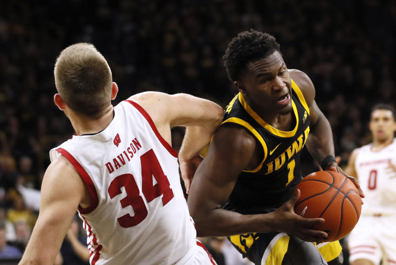 Iowa guard Joe Toussaint is fouled by Wisconsin guard Brad Davison (34) while driving to the basket during the second half of an NCAA college basketball game, Monday, Jan. 27, 2020, in Iowa City, Iowa. Iowa won 68-62. (AP Photo/Charlie Neibergall)