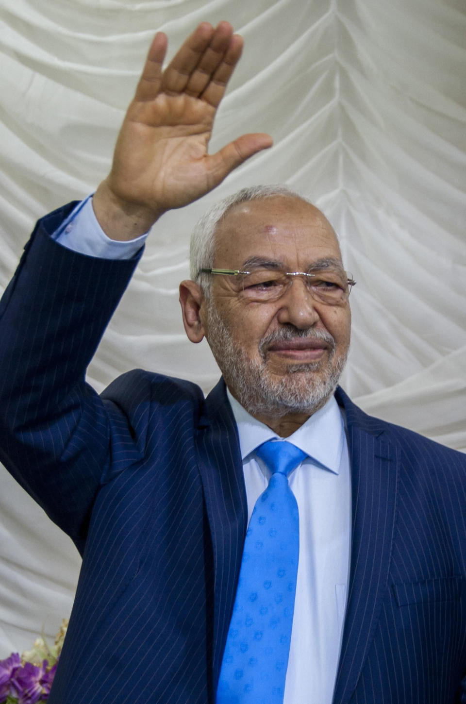 """File - In this April 16, 2018, photo, Tunisia's Islamist party leader and parliament speaker Rached Ghannouchi waves to supporters during a campaign rally in Tunis, Tunisia, Saturday, April 14, 2018. Rached Ghannouchi said on Tuesday that his party is working to form a """"national front"""" to counter President Kais Saied's decision to suspend the legislature, fire top government officials and take control of the fragile democracy amid the country's multi-layered crisis. (AP Photo/Hassene Dridi, File)"""