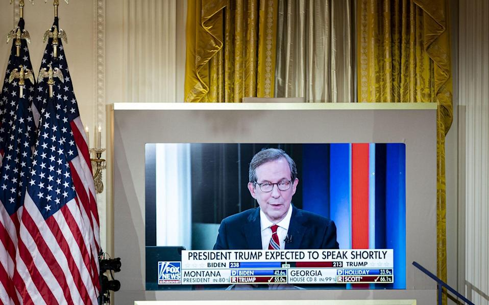 Chris Wallace, Fox News anchor, is displayed on a monitor during an election night party in the East Room of the White House