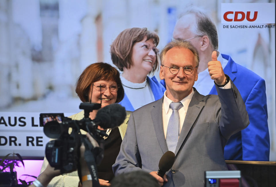 Saxony-Anhalt state governor Reiner Haseloff of Merkel's Christian Democratic Union party, CDU, and his wife Gabriele react, at the CDU election party, after the state election in Magdeburg, Germany, Sunday, June 6, 2021 . The election for the new state parliament in Saxony-Anhalt was the last state election before the federal election in September 2021. (Bernd Von Jutrczenka/dpa via AP)
