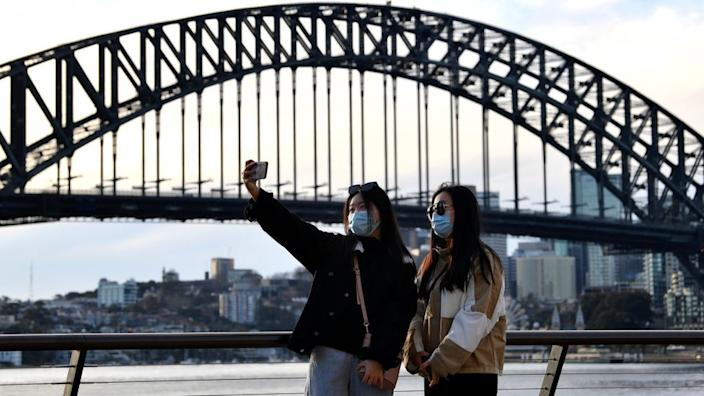 Chinese wearing masks take a selfie in front of the Sydney Harbor Bridge