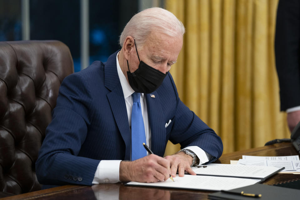 FILE - In this Feb. 2, 2021, file photo president Joe Biden signs an executive order on immigration, in the Oval Office of the White House in Washington. The Biden administration is facing growing questions about why it wasn't more prepared for an influx of migrants at the southern border. The administration is scrambling to build up capacity to care for 14,000 young undocumented migrants now in federal custody — and more likely on the way. (AP Photo/Evan Vucci, File)