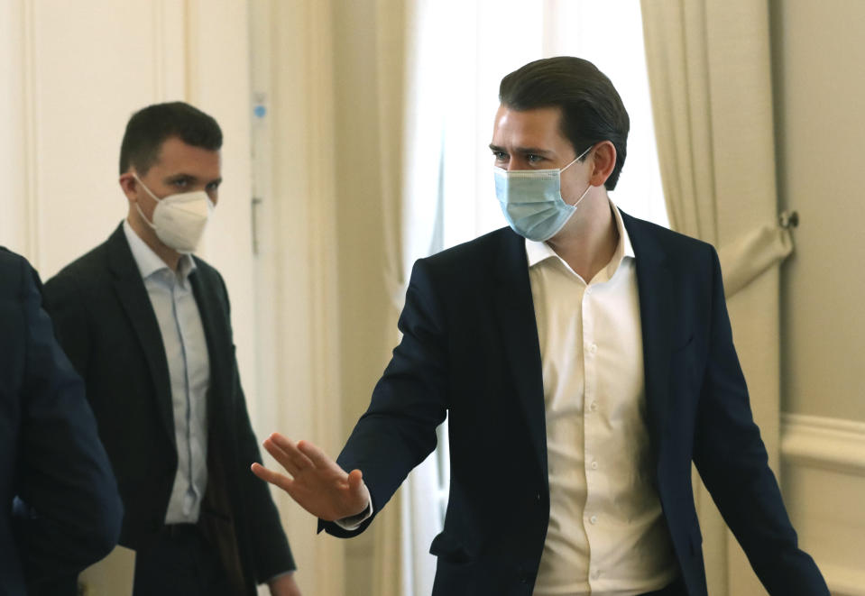 Austrian Chancellor Sebastian Kurz with a face mask walks at the federal chancellery in Vienna, Austria, Sunday, Jan. 17, 2021. The Austrian government has moved to restrict freedom of movement for people, in an effort to slow the onset of the COVID-19 coronavirus. (AP Photo/Ronald Zak)