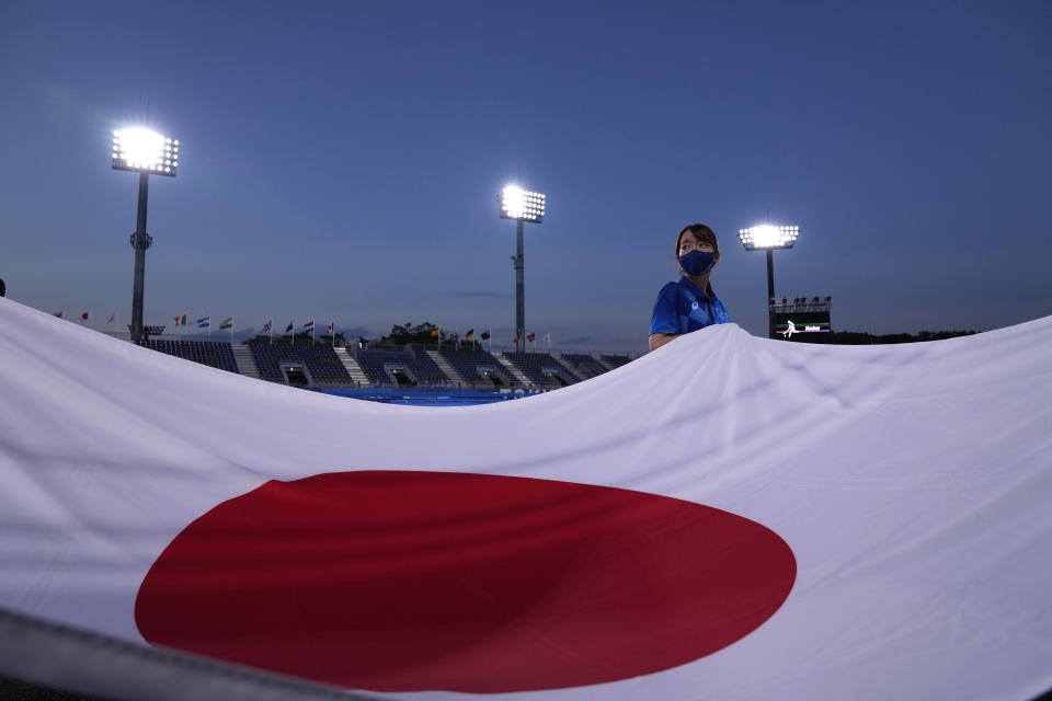 A flag bearer carries the flag of Japan before a men's field hockey match between Japan and Argentina at the 2020 Summer Olympics, Sunday, July 25, 2021, in Tokyo, Japan. (AP Photo/John Locher)a