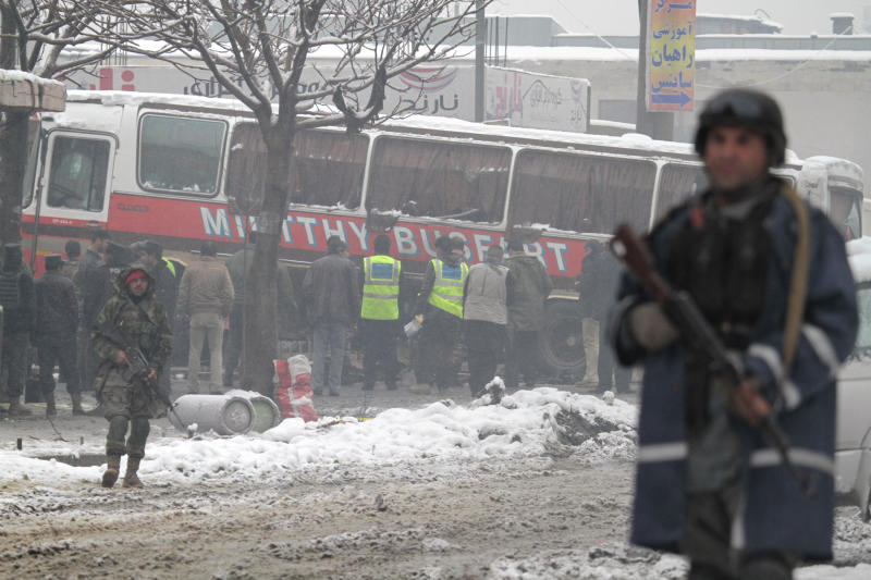 Afghan security men stand guard at the scene of a suicide attack in Kabul, Afghanistan, Wednesday, Feb. 27, 2013. A man wearing a black overcoat and carrying an umbrella as a shelter against the heavy snow crossed a street in the Afghan capital early Wednesday morning toward an idling bus filled with Afghan soldiers, where he laid down and wiggled underneath. Then he exploded, engulfing the undercarriage of the bus in flames. (AP Photo/Musadeq Sadeq)