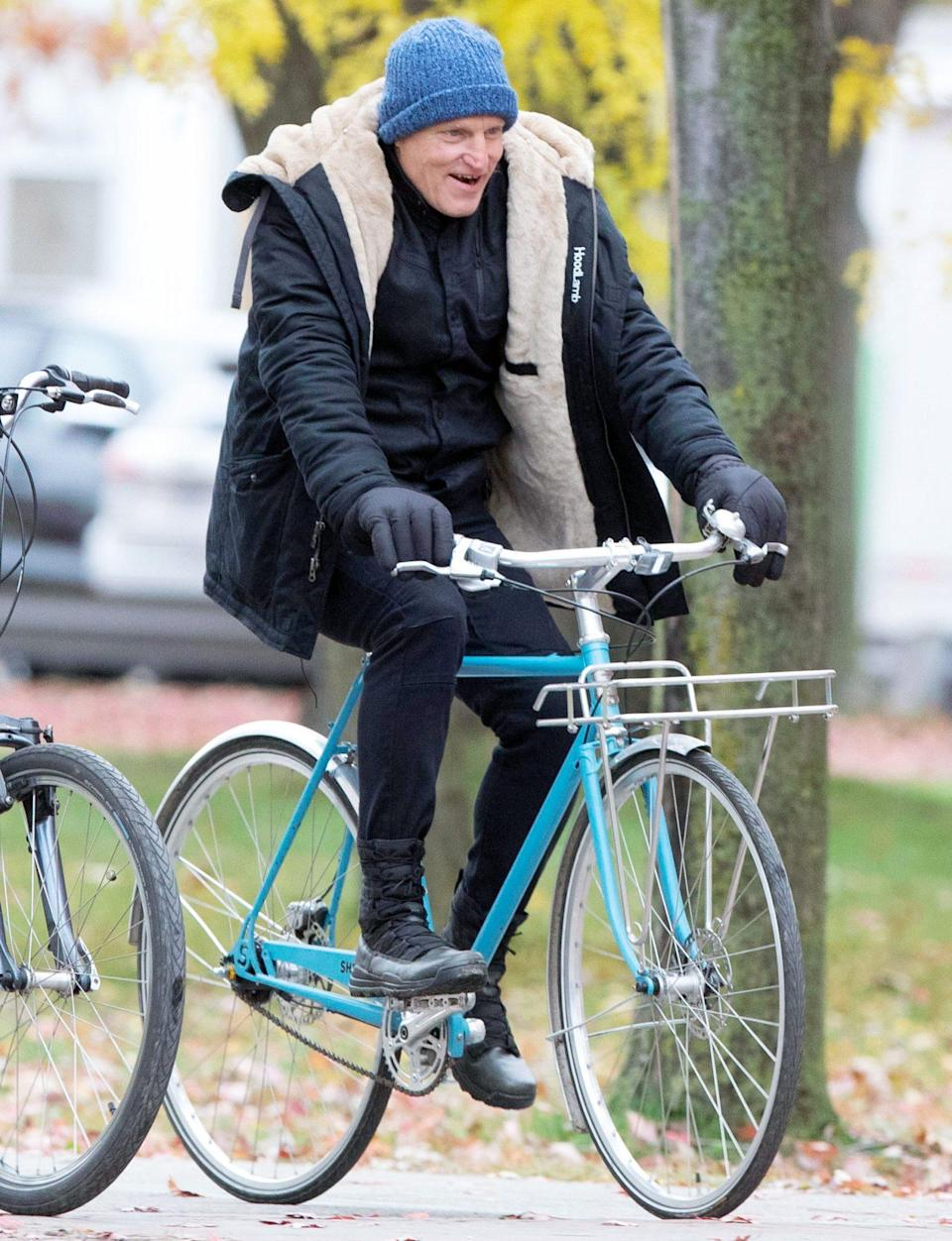 <p>Woody Harrelson bundles up as he rides a bike to the set of <i>The Man from Toronto </i>on Monday in Toronto. </p>