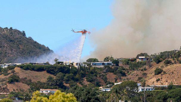 PHOTO: A helicopter makes a water drop as flames threaten homes on a ridgeline in the Pacific Palisades area of Los Angeles, Oct. 21, 2019. (Reed Saxon/AP)