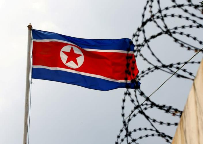 FILE PHOTO: A North Korea flag flutters next to concertina wire at the North Korean embassy in Kuala Lumpur