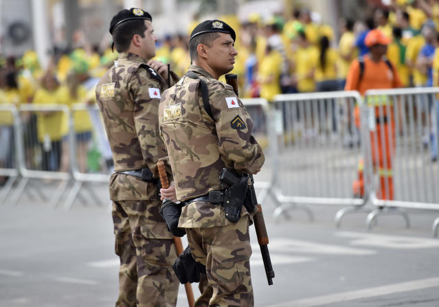 Special forces police watches Brazilian and German football fans outside the stadium prior the World Cup semifinal soccer match between Brazil and Germany at the Mineirao Stadium in Belo Horizonte, Brazil, Tuesday, July 8, 2014. (AP Photo/Martin Meissner)