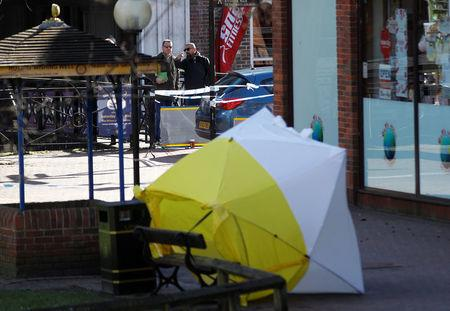 Local officials survey the scene as the forensic tent, covering the bench where Sergei Skripal and his daughter Yulia were found, is blown out of position in the centre of Salisbury, Britain, march 8, 2018. REUTERS/Peter Nicholls