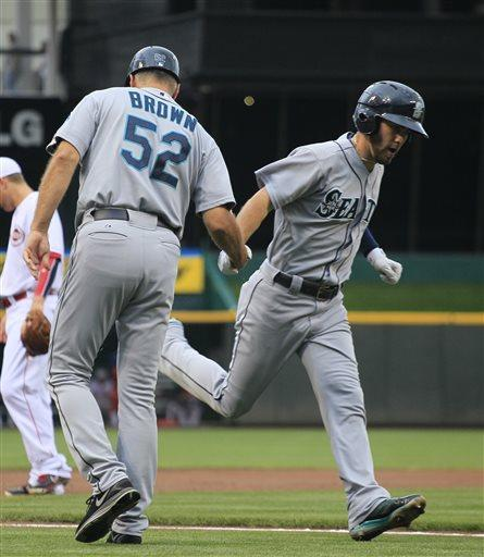 Seattle Mariners' Nick Franklin is congratulated by third base coach Daren Brown as he heads to home plate after hitting a two-run home run off Cincinnati Reds' Mike Leake in the first inning of their baseball game in Cincinnati, Friday July 5, 2013. (AP Photo/Tom Uhlman)
