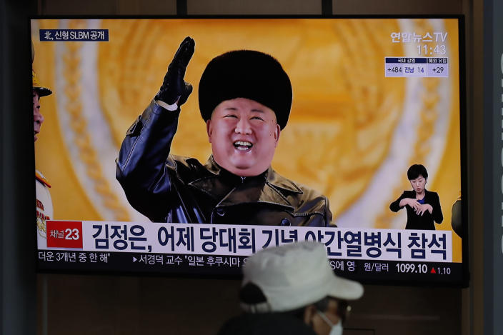 """A man wearing a face mask sits in front of a TV screen showing North Korean leader Kim Jong Un, at the Seoul Railway Station in Seoul, South Korea, Friday, Jan. 15, 2021. The letters read """"Kim Jong Un attended stage in Thursday night's parade celebrating a ruling party congress."""" (AP Photo/Lee Jin-man)"""