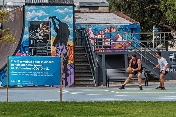 Two men not observing social distancing playing basketball in Prahran with a sign outside the court reading that the court is closed.