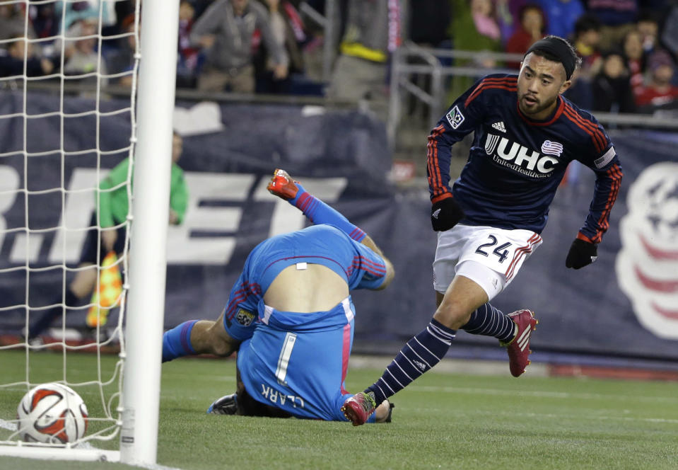 New England Revolution midfielder Lee Nguyen, right, scores as Columbus Crew goalkeeper Steve Clark, center, falls during the first half of an MLS soccer playoff game, Sunday, Nov. 9, 2014, in Foxborough, Mass. (AP Photo/Steven Senne)
