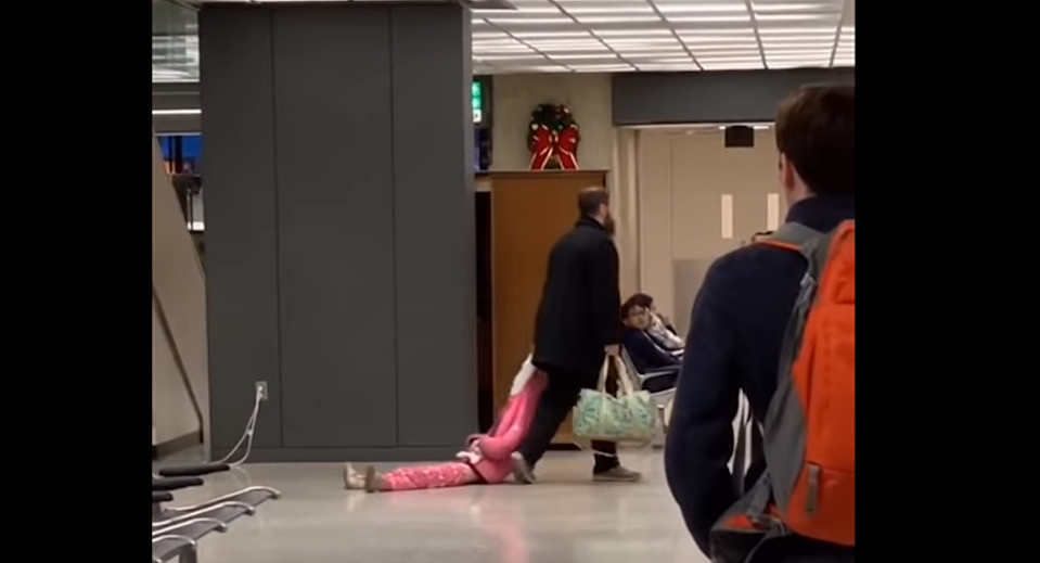 A young girl being dragged through Dulles International Airport by her dad, as captured on video New Year's Day. (Photo: JF_112 via Reddit)