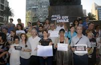People in Montevideo hold signs to show solidarity for the victims of the attack on Charlie Hebdo