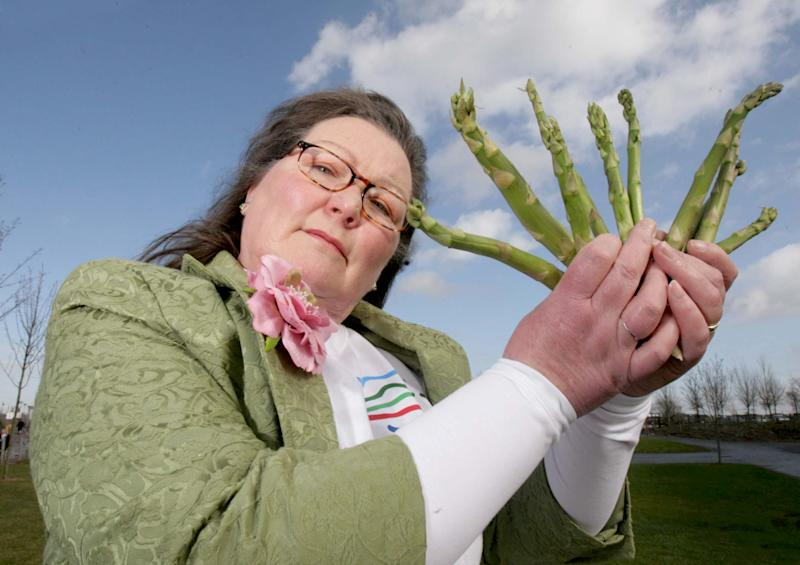 Jemima Packington holding a bunch of asparagus stalks. [Photo: SWNS]