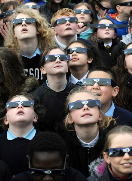 School children gather to view the partial solar eclipse at the Glasgow Science Centre in Glasgow, Scotland on March 20, 2015 (AFP Photo/Andy Buchanan)