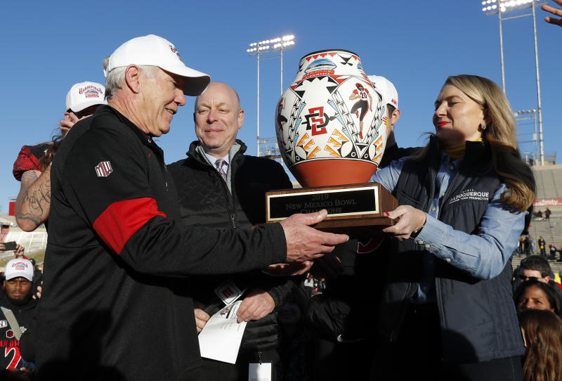 San Diego State coach Rocky Long, left, receives the trophy after his team beat Central Michigan in the New Mexico Bowl NCAA college football game on Saturday, Dec. 21, 2019 in Albuquerque, N.M. (AP Photo/Andres Leighton)