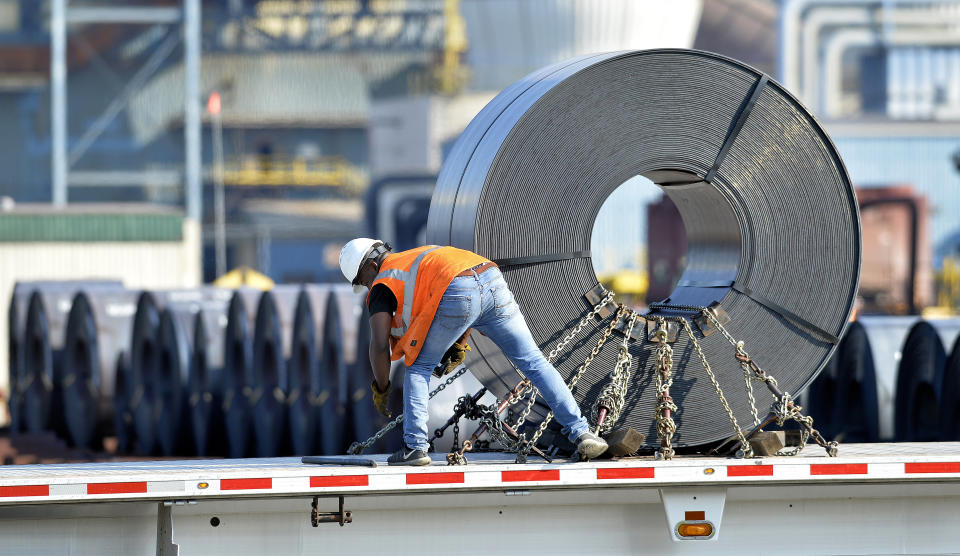 In this July 25, 2018, photo a truck driver chains down a roll of steel to his flatbed at the NUCOR Steel Gallatin plant in Ghent, Ky. The rolls, weighing as much as 20 tons, are transported one at a time. On Wednesday, Aug. 15, the Federal Reserve reports on U.S. industrial production for July. (AP Photo/Timothy D. Easley)