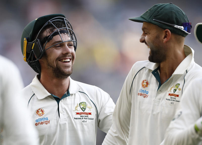 Travis Head and Nathan Lyon laugh and celebrate after combining to take a wicket.