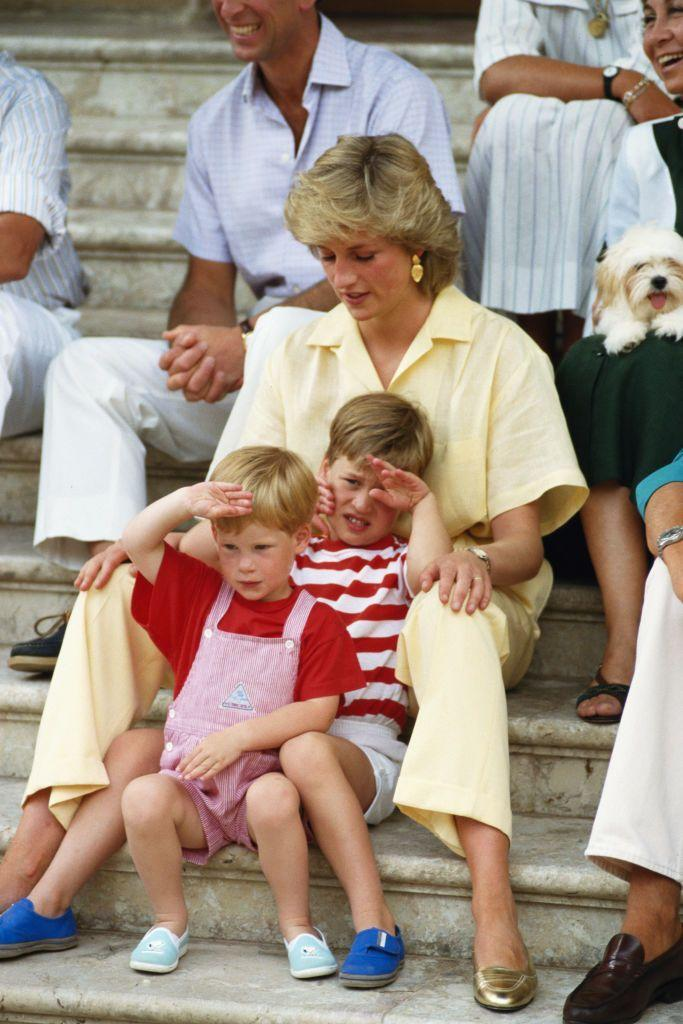 <p>A small Prince Harry and Prince William saluted in coordinating red and white striped outfits. Princess Diana complemented their looks in a pale yellow ensemble. </p>