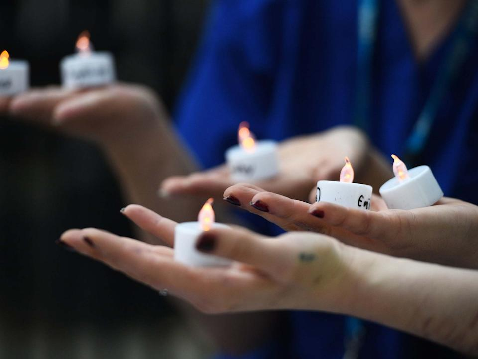 Nurses hold candles bearing the names of 235 health and social care workers that have died from coronavirus during a vigil outside Downing Street: PA
