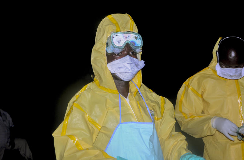 Workers wearing protective clothing prepare to bury Agnes Mbambu who died of Ebola, the 50-year-old grandmother of the 5-year-old boy who became Ebola's first cross-border victim, in the village of Karambi, near the border with Congo, in western Uganda Thursday, June 13, 2019. The two were part of a larger Congolese-Ugandan family who crossed to Congo when one of their elders there, a pastor, became sick with Ebola and they crossed back into Uganda on June 9 via a footpath not patrolled by border authorities. (AP Photo/Ronald Kabuubi)