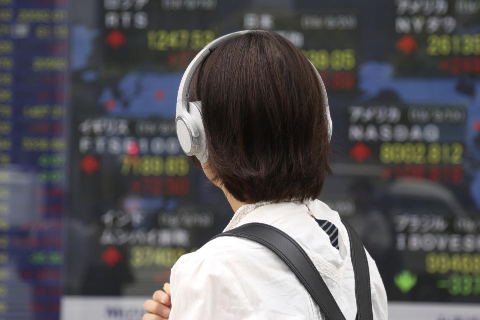 A woman looks at an electronic stock board of a securities firm in Tokyo, Tuesday, Aug. 20, 2019. Asian shares were mostly higher Tuesday after Wall Street rallied on the U.S. decision to give Chinese telecom giant Huawei another 90 days to buy equipment from American suppliers. (AP Photo/Koji Sasahara)