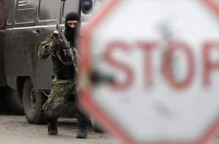 A pro-Russian rebel holds his rifle at a checkpoint near a Ukrainian airbase in Kramatorsk