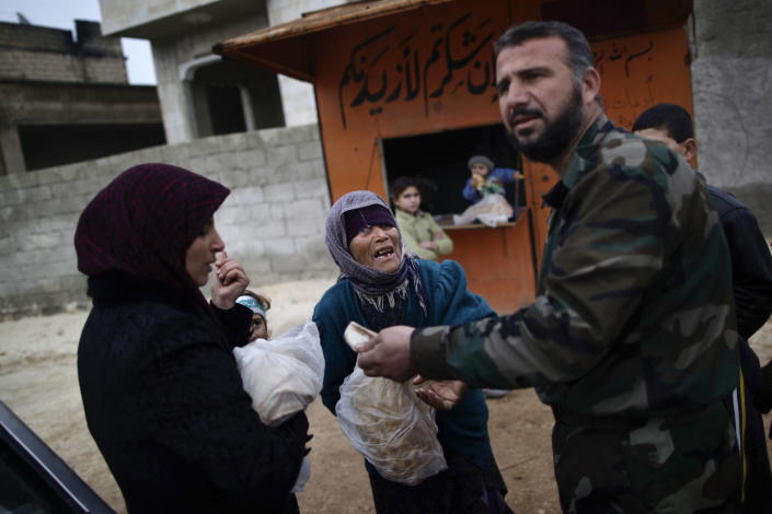 In this Thursday, Dec. 13, 2012, photo, a woman asks a Free Syrian Army fighter to sell her bread, in Maaret Misreen, near Idlib, Syria. The town is broke, relying on a slowing trickle of local donations. The rebels, a motley crew of laborers, mechanics and shopowners, have little experience in government. President Bashar Assad's troops still control the city of Idlib a few miles away, making area roads unsafe and keeping Maaret Misreen cut off from most of Syria.(AP Photo/Muhammed Muheisen)