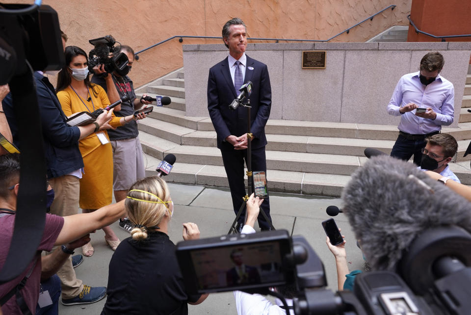 """California Gov. Gavin Newson listens to a question while meeting with reporters after casting his recall ballot at a voting center in Sacramento, Calif., Friday, Sept. 10, 2021. The last day to vote in the recall election is Tuesday Sept. 14. A majority of voters must mark """"no"""" on the recall to keep Newsom in office. (AP Photo/Rich Pedroncelli)"""
