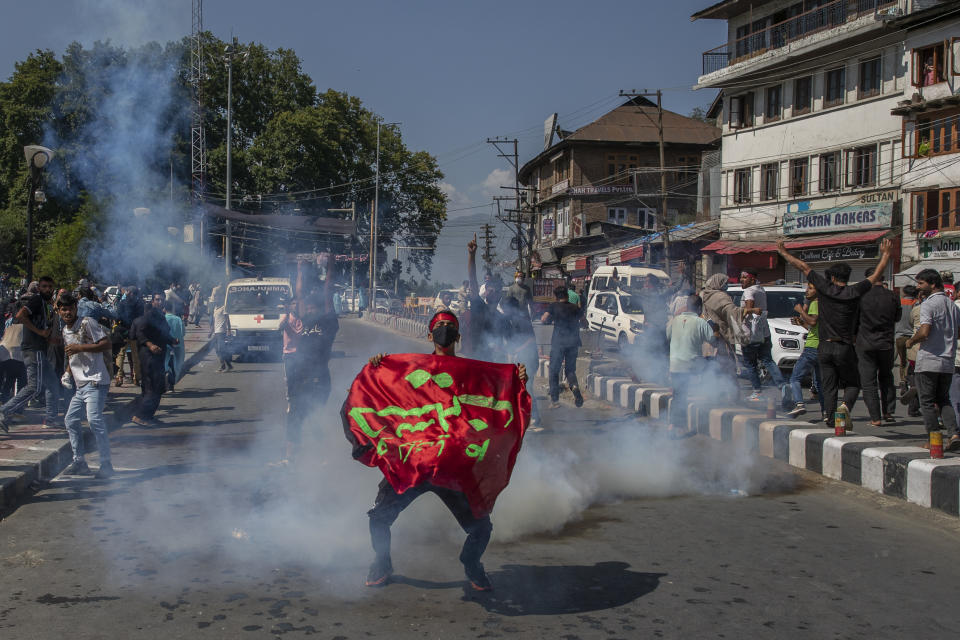 A Kashmiri Shiite Muslim holds religious banner as he stands amid tear gas smoke fired by Indian police man during a religious procession in central Srinagar, Indian controlled Kashmir, Tuesday, Aug. 17, 2021. Police in Indian-controlled Kashmir on Tuesday fired tear gas and warning shots to disperse hundreds of Shiite Muslims, while detaining dozens who attempted to participate in processions marking the Muslim month of Muharram. (AP Photo/Dar Yasin)