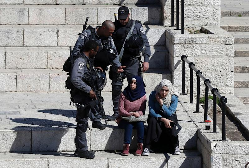 Israeli policemen ask Palestinian women for their documents at Damascus Gate in the Old City of Jerusalem on February 17, 2016 (AFP Photo/Ahmad Gharabli)