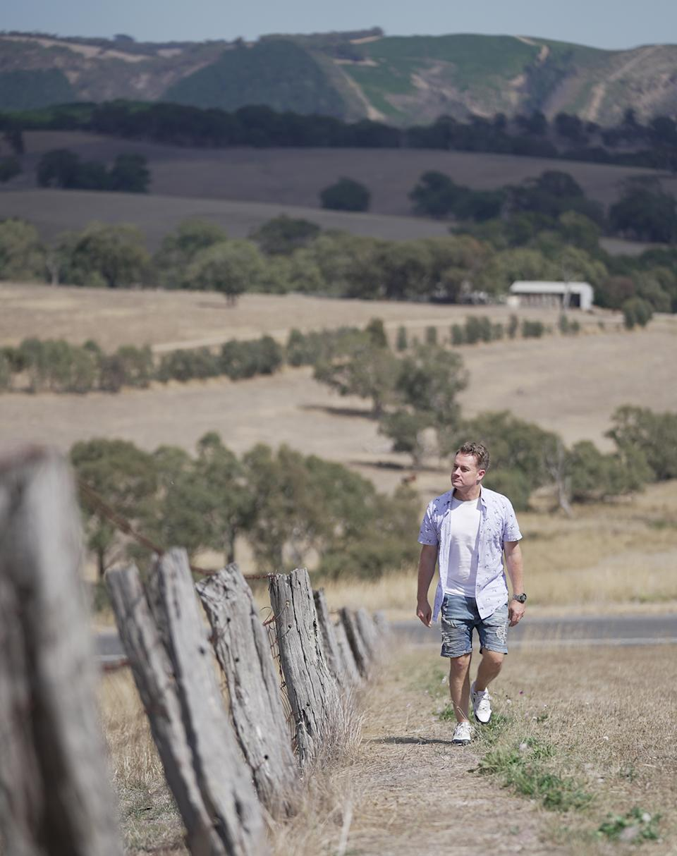 Grant Denyer walking along a fence on a farm in Victoria in an episode of SBS' Who Do You Think You Are?