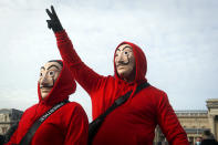 People wearing masks take part in a hospitality sector workers protest, in Budapest, Hungary, Sunday, Jan. 31, 2021. Protesters gathered at a central square in Hungary's capital of Budapest on Sunday demanding a rethinking of the country's lockdown restrictions. As the lockdown limiting restaurants to take-away service approaches the three-month mark, many business owners complain that they have received little to none of the government's promised financial assistance while other businesses like shopping malls and retail stores have been permitted to remain open. (AP Photo/Laszlo Balogh)