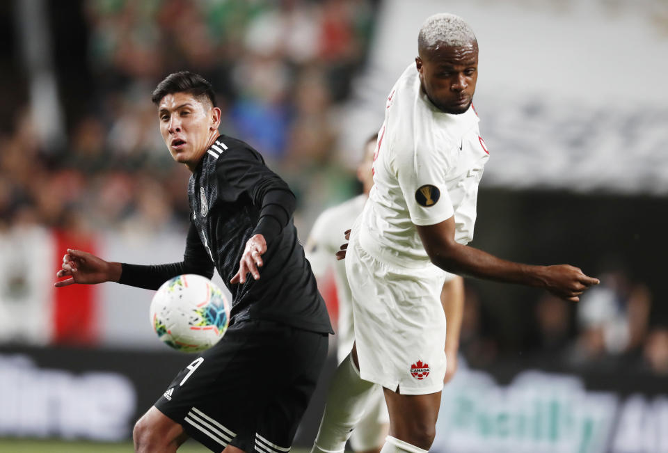 Mexico defender Edson Alvarez, left, fights for control of the ball with Canada forward Cyle Larin during the first half of a CONCACAF Gold Cup soccer match Wednesday, June 19, 2019, in Mile High Stadium in Denver. (AP Photo/David Zalubowski)