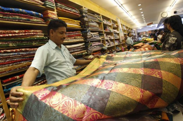 A vendor sells sari ahead of Deepavali at Little India in Singapore October 31, 2013. The Hindu community will celebrate the Festival of Lights known as Diwali or Deepavali, on November 2. REUTERS/Edgar Su (SINGAPORE - Tags: RELIGION BUSINESS TEXTILE)