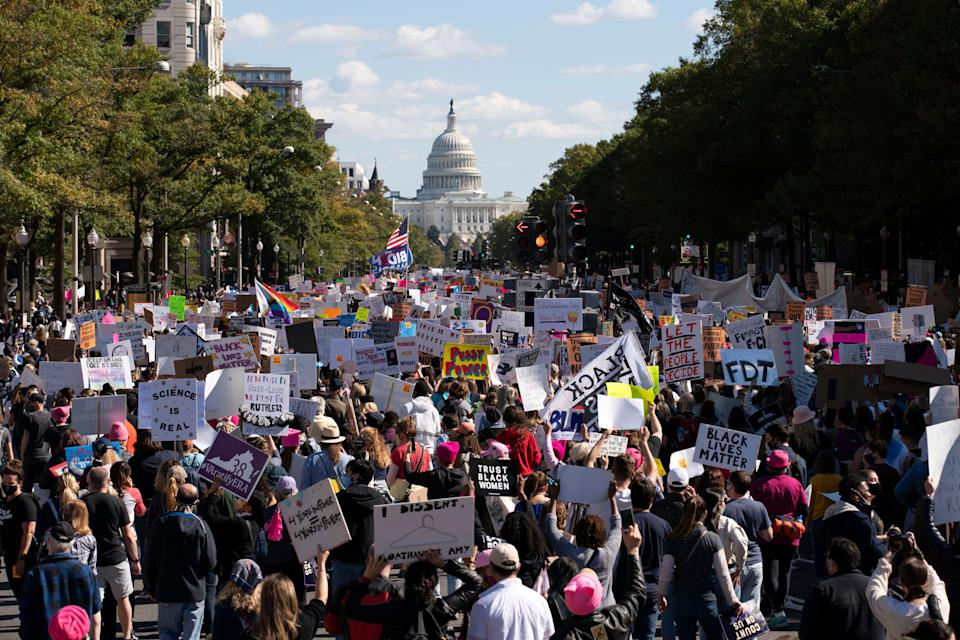 With the U.S Capitol in the back ground demonstrators march on Pennsylvania Avenue during the Women's March in Washington, Saturday, Oct. 17, 2020.