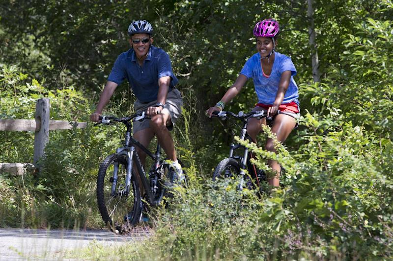 President Barack Obama, with daughter Malia, rides bicycles in Manuel F. Correllus State Forest, after first lady Michelle Obama, with daughter Sasha, not pictured, passed by first, Friday, Aug. 16, 2013, in West Tisbury, Mass., during their family vacation on the island of Martha's Vineyard. (AP Photo/Jacquelyn Martin)