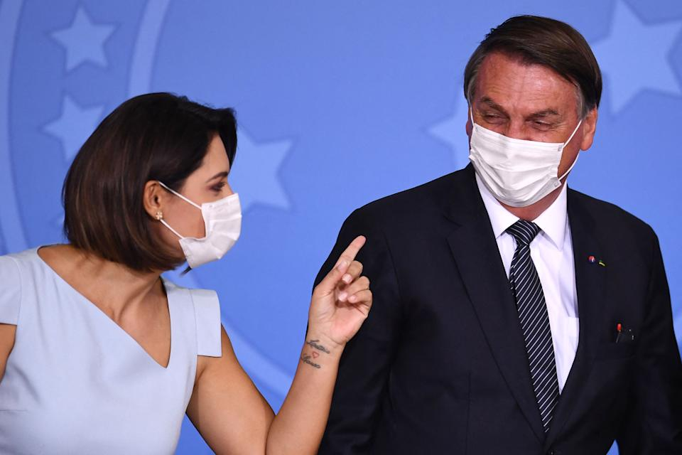 Brazilian President Jair Bolsonaro (R) and First Lady Michelle Bolsonaro speak during the announcement that the public healthcare system will cover expanded heel prick tests at Planalto Palace, in Brasilia, on May 26, 2021. (Photo by EVARISTO SA / AFP) (Photo by EVARISTO SA/AFP via Getty Images)