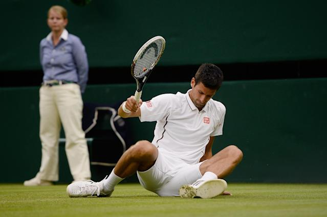 LONDON, ENGLAND - JUNE 27: Novak Djokovic of Serbia slips on the grass during his Gentlemen's Singles second round match against Bobby Reynolds of the United States of America on day four of the Wimbledon Lawn Tennis Championships at the All England Lawn Tennis and Croquet Club on June 27, 2013 in London, England. (Photo by Dennis Grombkowski/Getty Images)
