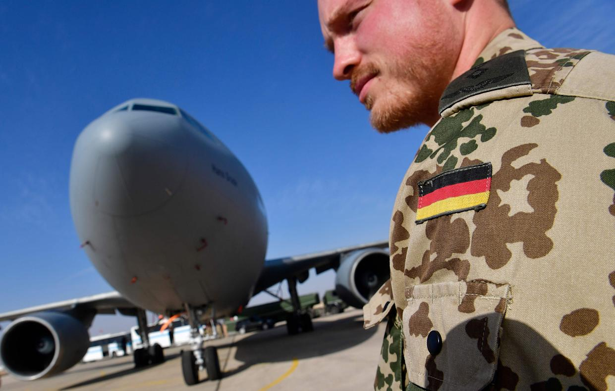 Image: A member of the German contingent standing next to a German air force Airbus A-310 aerial refueling tanker aircraft at the Al Azraq air base in Jordan.