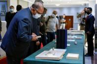 Officials look at artifacts seized by the U.S. government and returned to Iraq, which are on display at the Ministry of Foreign Affairs in Baghdad